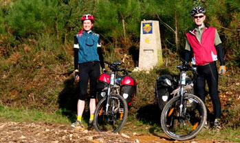 Cyclists standing next to a Camino de Santiago signpost