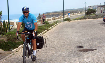 Cyclist on cobble street on the coast in Ericeira, Portugal