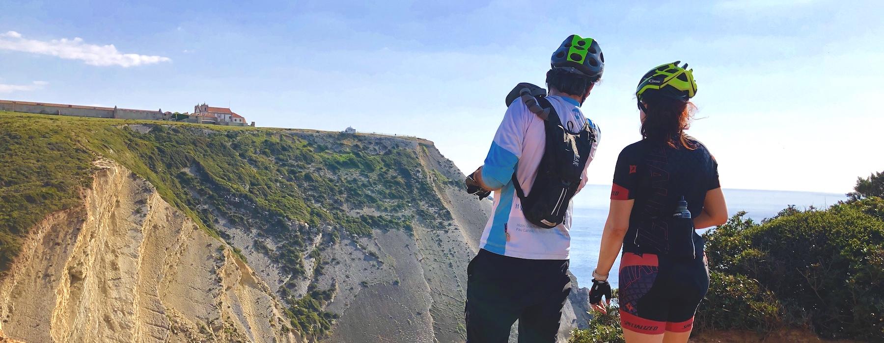 Bikers looking over cliff shore