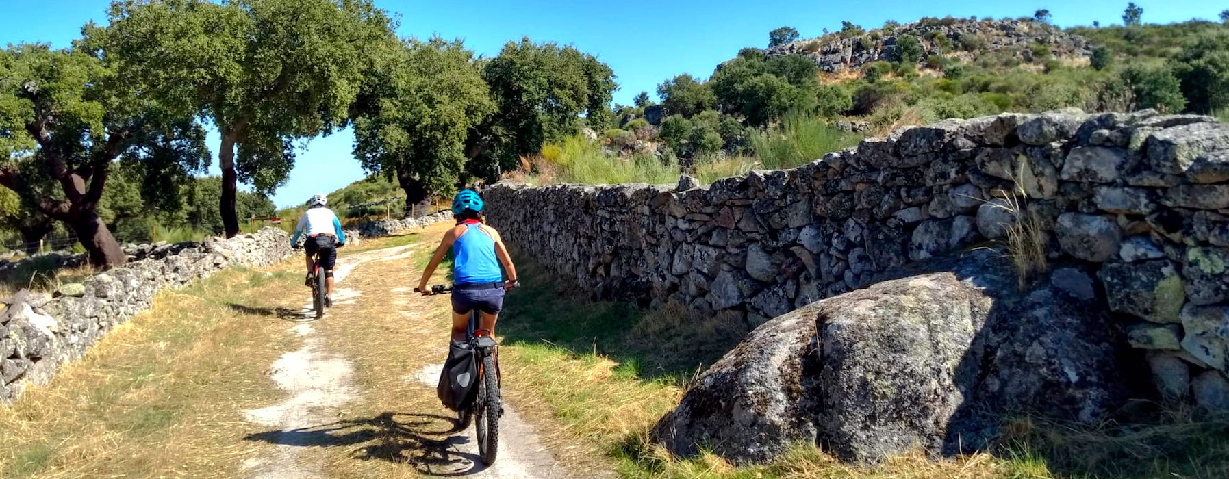 Bikers in trail with traditional stone wall